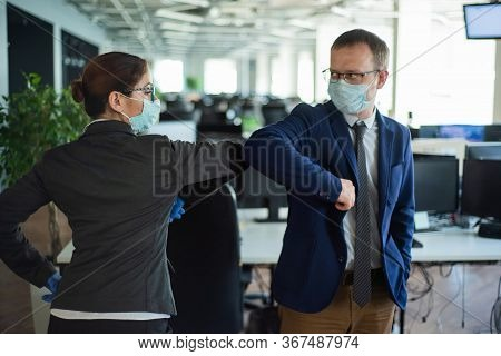 Office Workers Shake Hands When Meeting And Greet Bumping Elbows. A New Way To Greet The Obstructing
