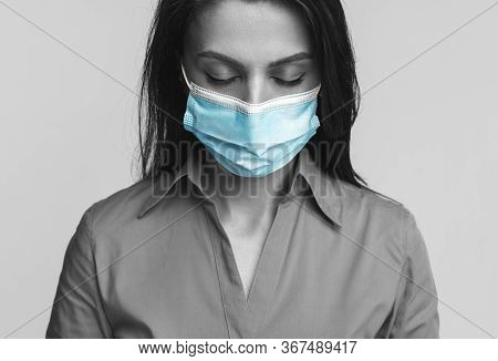 Black And White Unhappy Woman In Blue Surgical Mask Closing Eyes And Grieving During Coronavirus Pan
