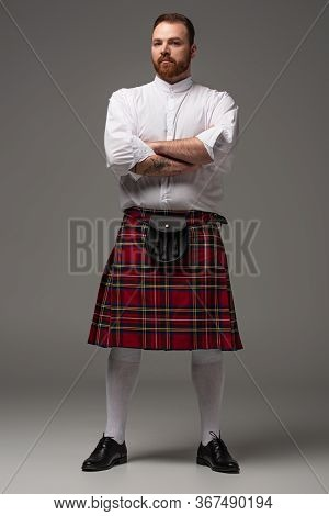 Scottish Redhead Man In Red Kilt With Crossed Arms On Grey Background