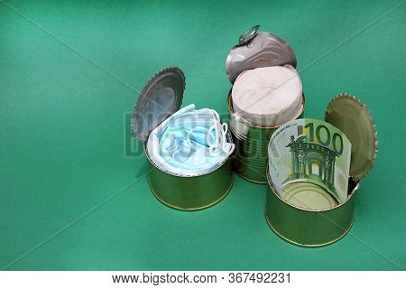An Open Metal Cans With Medical Masks, Toilet Paper, And A 100-euro Bill. Concept Of Economic Crisis