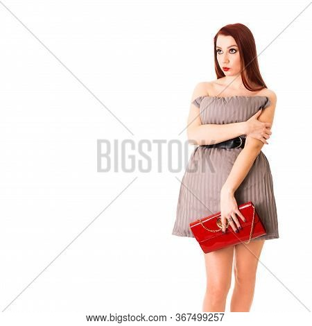 Surprised Naked Sexy Red-haired Girl With A Red Bag Hides Behind A Beige Pillow On A White Backgroun
