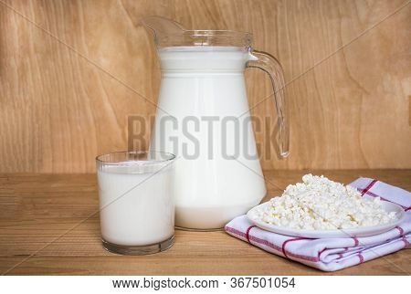 Tasty Fresh Milk On A White Wooden Background. A Jug Of Milk And A Glass Of Milk. Copy Space