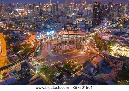 Aerial View Of Victory Monument With Car Light Trails On Busy Street Road. Roundabout In Bangkok Dow