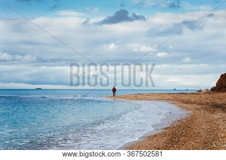 Oceanside. On A Sand Spit Stands A Guy And Looks At The Horizon