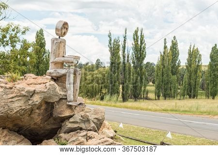 Clocolan, South Africa - March 20, 2020: A Wooden Log Man Next To Road R26 At The Cabin Road Stall,