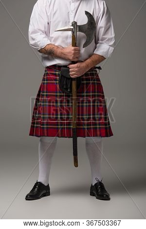 Cropped View Of Scottish Man In Red Kilt With Battle Axe On Grey Background