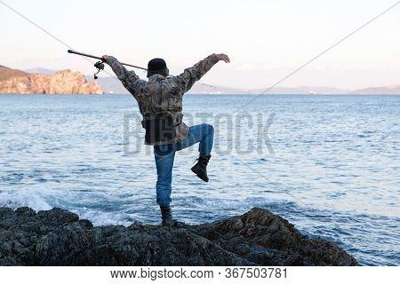 Fisherman meditates fishing on sea rocks in the evening