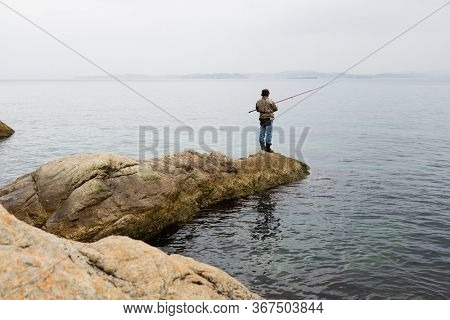 Fisherman on sea fishing on the rocks in the early morning.