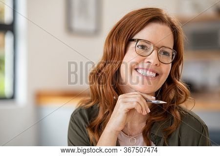 Thoughtful mature woman with hand on chin wearing eyeglasses and working at home. Happy mid writer wearing spectacles and holding pen thinking. Happy blogger contemplating and writing with copy space.