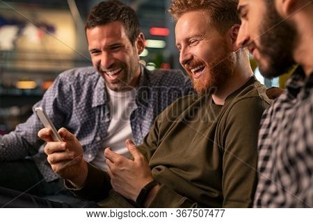 Friends meeting in bar, using smartphone. Happy young friends sitting on couch and watching streaming on mobile phone while laughing. Mid man with friends holding smart phone while watching video.