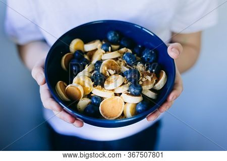 Close- Up Of Mini Pancake Cereal, Mini Pancakes In A Dark Blue Bowl With Maple Sirup Honey With Blue