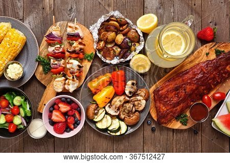 Summer Bbq Or Picnic Food Table Scene. Selection Of Grilled Meats, Vegetables, Fruits, Salad And Pot