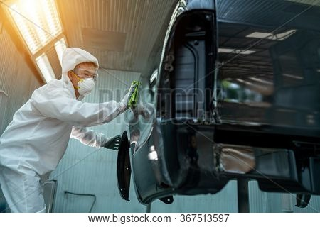 The Expert Is Painting The Car In The Paint Room.