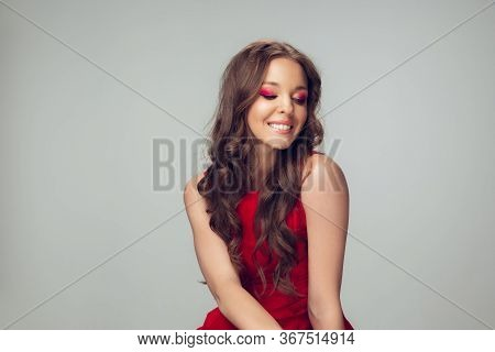 Beautiful Young Woman With Long Healthy Curly Hair And Bright Make Up Wearing Red Dress Isolated On
