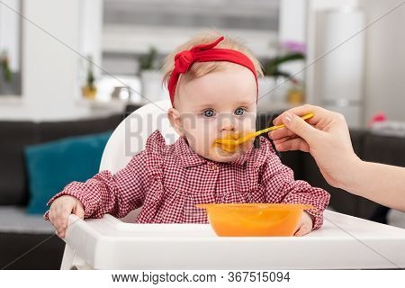 Mother Feeding Baby Sitting In Chair