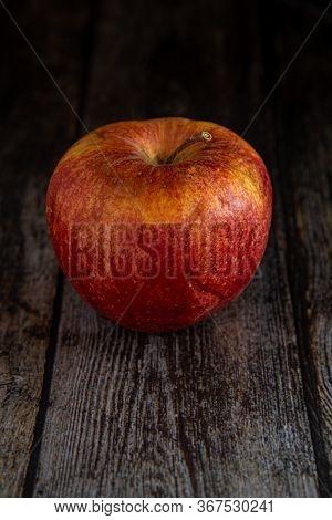 Red Wilted Rotten Apple With A Wooden Surface Background