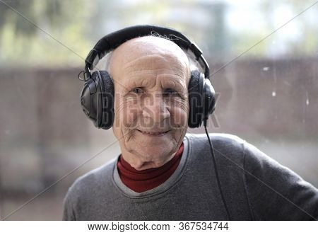 elderly man listens to music with headphones