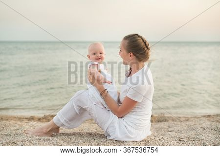 Portrait Of Mum And Baby Daughter On Sandy Shores Of Sea Background. Happy Mother And Child.