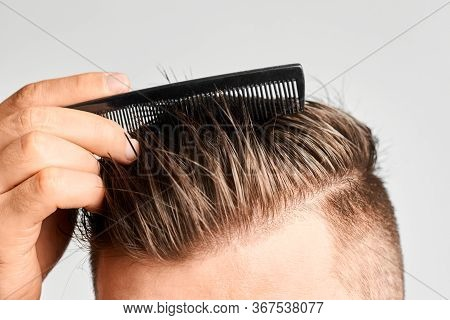 Man Combing His Clean Hair With Plastic Comb. Hair Styling At Home. Concept Of Hair Loss Or Or Dandr