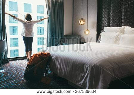 Backpacker Female Accomodating In 5 Stars Luxury Hotel. She Opening A Whole Wall Window Curtains To