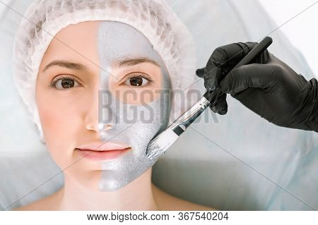 Nice Woman Looks Directly Into The Camera While Lying On A Cosmetology Table And Applying A Silver B