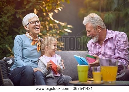 Happy grandparents spending time with smiling granddaughter. Family generations concept.
