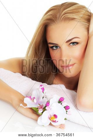 Closeup portrait of pretty woman in spa salon, beautiful young lady with blond hair hold pink orchid flower, cute girl with natural makeup, day spa, beauty treatment, skincare, aroma therapy