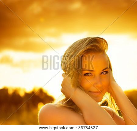 Picture of beautiful female over sunset, closeup portrait of cute romantic girl, attractive blond woman enjoying autumn yellow sunlight, pretty young lady outdoors rejoice of warm  weather fall