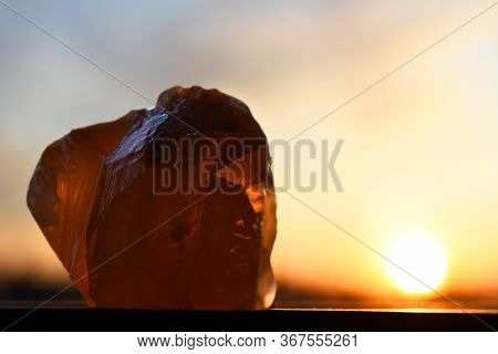 N Image Of A Large Honey Calcite Crystal On A Window Ledge At Sunset.