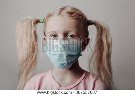 Portrait Of Caucasian Blonde Girl In Sanitary Face Mask. Preschool Child Wearing Protective Mask Aga