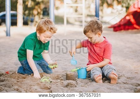 Two Caucasian Children Sitting In Sandbox Playing With Beach Toys. Little Boys Friends Having Fun To