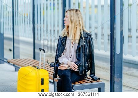 Young Blonde Woman Traveler Millennial Looking Aside Sitting On Bench On Bus Or Tram Stop With Yello