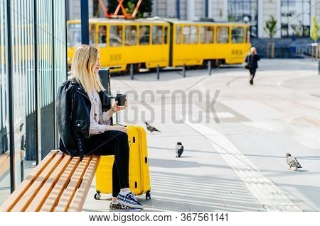 Side View Of Young Blonde Woman Traveler Millennial With Big Yellow Suitcase On Bus Or Tram Stop Wai