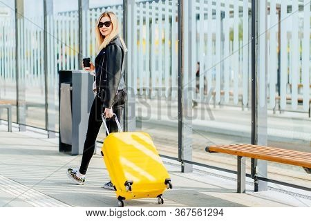 Rear View Of Young Positive Blonde Woman Traveler Millennial Drins Coffee To Go And Carryng Her Yell