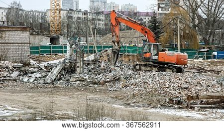 Hydraulic Crusher Excavator Machine With Attached Hydraulic Jaw At City Demolition Site After Buildi