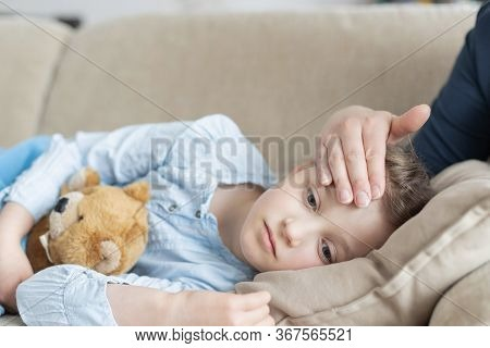 A Sick And Sad Cute Girl Lies On A Sofa With A Soft Toy And Her Mother Checks The Heat Or Temperatur