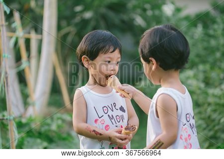 Twin Boy Smile Happy And Holding Ice Cream Chocolate In Hand. Twin Boy Eating Ice Cream With Dirty F