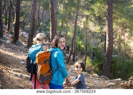 Two Women And A Child Walk In The Forest. Hiking With Children. Lgbt Family. A Girl With A Backpack
