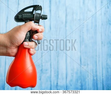 Sprayer For Plants In A Male Hand On A Blue Background