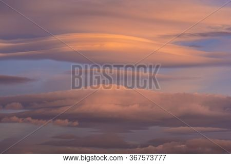 Lenticular Clouds Over The Sky At Dawn With Reddish And Orange Colors