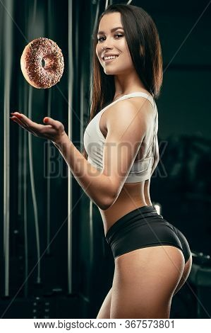 Fitness Woman With Donut At Workout In The Gym