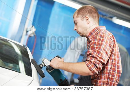 auto mechanic worker polishing car at automobile repair and renew service station shop by power buffer machine