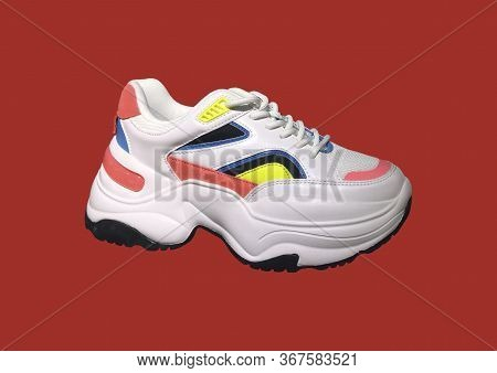 White Platform Sneakers With Bright Color Accents Pattern On Red Background. Close View Of Fashion C