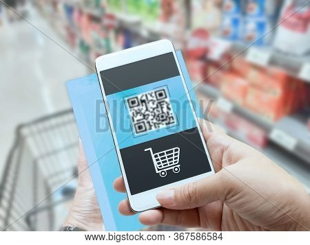 Online Order Grocery Shopping On Touch Screen Concept. Woman Hand Holding Smart Phone And Scanning Q