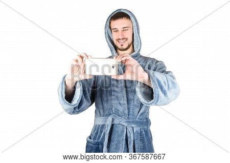 Portrait Of Young Caucasian Bearded Man In Blue Bathrobe Takes Photo With Smartphone Isolated On Whi