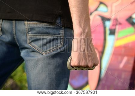 Back View Of Young Caucasian Man With Brass Cnuckle On His Hand Against Ghetto Brick Wall With Graff