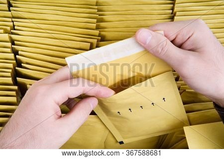 Self Sealed Mailing Envelope Quality Inspection. Male Hands Open One Yellow Bubble Mailer Out Of A B