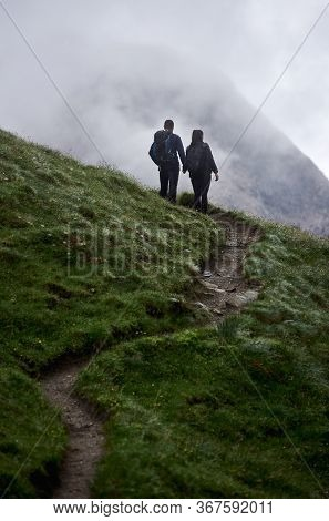 Back View Of Male Traveller And Girlfriend Standing On Grassy Hillside Path And Holding Hands. Lovin