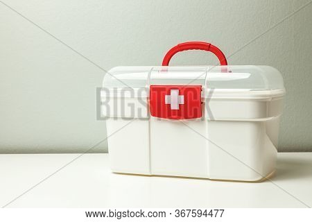 First Aid Kit. White Box With A Cross And A Red Clasp On A Gray Background