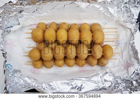 Fresh Whole Baby Potatoes In Their Jackets Threaded Onto Wooden Skewers For Grilling Heaped On Silve